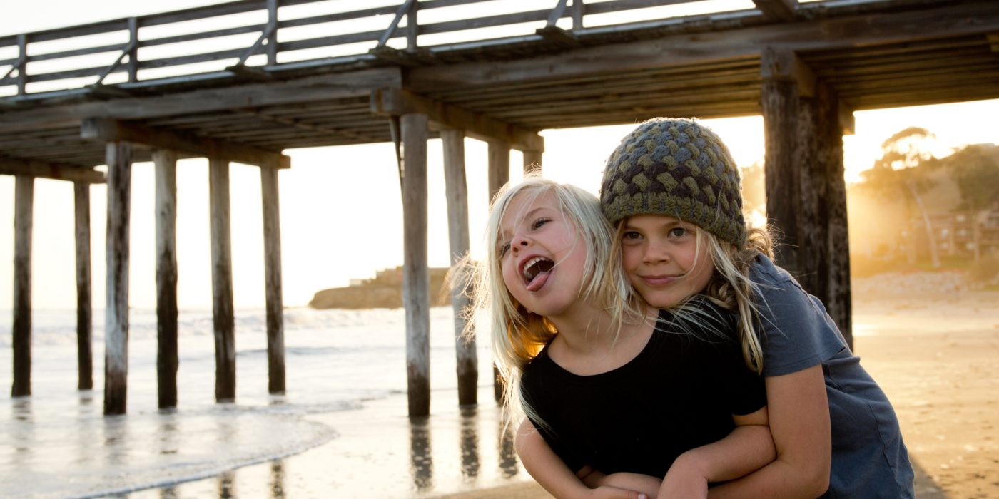 Kids Hugging during Golden Hour by Avila Pier