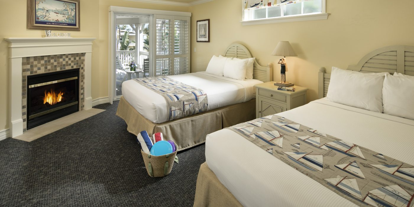 Avila Lighthouse Suites Owners Suite Bedroom with Two Queen Beds and Fireplace